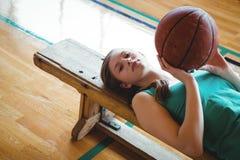 Портрет женщины при баскетбол лежа на стенде в суде Стоковая Фотография