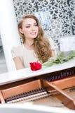 Портрет женщины при красная роза играя рояль Стоковые Изображения