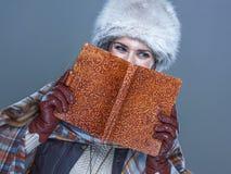 Портрет женщины пряча за книгой и смотря космос экземпляра Стоковое фото RF