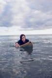 Портрет женщины плавая над surfboard в воде Стоковая Фотография