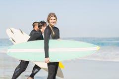 Портрет женщины серфера при surfboard стоя на пляже Стоковая Фотография RF