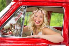 Портрет женщины сидя в винтажном автомобиле и усмехаться Стоковое Фото