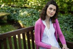 Портрет женщины сидя на скамейке в парке Стоковое Фото