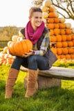 Портрет женщины сидя на стенде с тыквой на ферме Стоковые Изображения RF