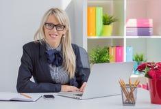 Портрет женщины сидя на столе в офисе Стоковое Фото