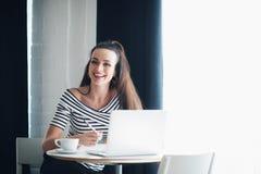 Портрет женщины смеясь над и смотря прочь с компьтер-книжкой в кафе Дама сидит на таблице около окна с чашкой Стоковая Фотография