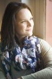 Портрет женщины смотря из окна Стоковое фото RF