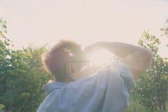 Портрет женщины смотря отсутствующую предпосылку захода солнца Стоковые Фото