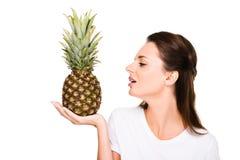 портрет женщины смотря свежий ананас в руке Стоковые Фотографии RF