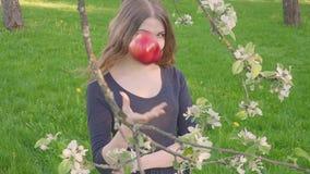 Портрет женщины стороны молодой красивой держа яблоко на природе лета предпосылки яблони весны зацветая Весна видеоматериал