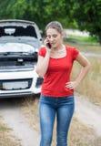 Портрет женщины стоя на сломленном автомобиле и говоря телефоном Стоковое фото RF