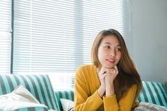 Портрет женщины счастливого домовладельца азиатской с сидеть совершенных зубов усмехаясь на софе в живущей комнате в интерьере до Стоковые Фотографии RF