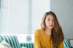Портрет женщины счастливого домовладельца азиатской с сидеть совершенных зубов усмехаясь на софе в живущей комнате в интерьере до Стоковое фото RF