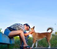 Портрет женщины с ее собакой играет на поле травы, они смотрят очень счастливыми и смешными Стоковые Фотографии RF