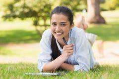 Портрет женщины с книгой и ручки в парке Стоковое фото RF