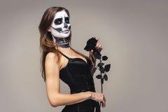 Портрет женщины с макияжем хеллоуина каркасным держа черный розовый цветок над серой предпосылкой стоковые фотографии rf