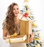 Портрет женщины с настоящим моментом кладет в коробку около рождественской елки Стоковая Фотография