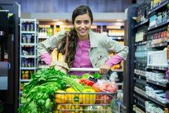 Портрет женщины с овощами в вагонетке покупок Стоковое Изображение RF