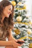 Портрет женщины с сотовым телефоном около рождественской елки Стоковая Фотография