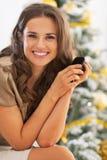 Портрет женщины с сотовым телефоном около рождественской елки Стоковые Изображения