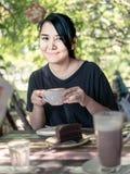 Портрет женщины усмехаясь с чашкой горячего капучино Стоковые Изображения RF