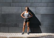 Портрет женщины фитнеса стоя на стене стоковая фотография rf
