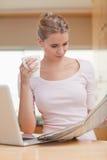 Портрет женщины читая газету пока имеющ чай Стоковые Изображения RF