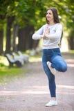 Портрет женщины yogi стоя в представлении Vrikshasana Стоковое Изображение
