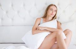 Портрет женщины yound унылой лежа на кровати в светлой комнате, инсомнии, похмелье, одиночестве стоковое изображение