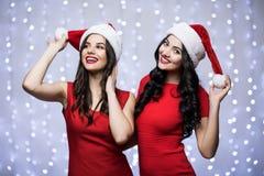 Портрет 2 женщин в шляпах santa и красное платье на bokeh освещают предпосылку Концепция рождества и Нового Года зимнего отдыха Стоковая Фотография RF