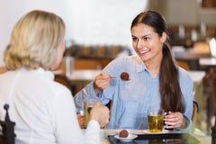 Портрет 2 женщин с чаем и шоколадами в кафе Стоковые Фото