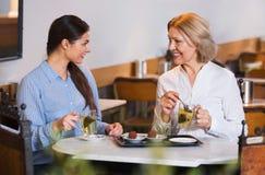 Портрет 2 женщин с чаем и шоколадами Стоковая Фотография