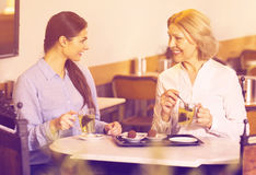 Портрет 2 женщин с чаем и шоколадами Стоковые Фото