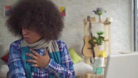 Портрет живя комнаты сидя на стиле Афро стиля причесок молодой женщины таблицы Афро-американском в шарфе, боли в горле и видеоматериал