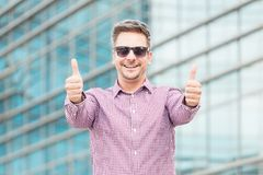 Портрет жизнерадостного бизнесмена с большими пальцами руки вверх перед организацией бизнеса стоковые фото