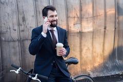 портрет жизнерадостного бизнесмена с кофе, который нужно пойти поговорить на smartphone Стоковая Фотография RF