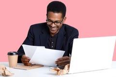 Портрет жизнерадостного мужского финансиста с темной кожей, носит стекла, имеет выражение вентилятора, подготавливает отчет, выпи стоковое изображение