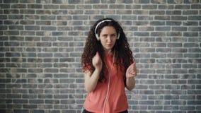 Портрет жизнерадостного танцора слушая музыку в наушниках танцуя ослаблять сток-видео