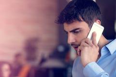 Портрет жизнерадостного усмехаясь работника офиса людей говоря на мобильном телефоне пока стоящ в современных размерах офиса Стоковое фото RF