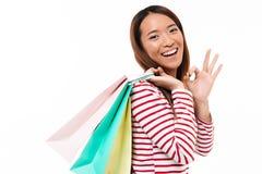 Портрет жизнерадостной азиатской девушки держа хозяйственные сумки Стоковое Фото