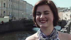 Портрет жизнерадостной девушки в запятнанном платье поет вдоль реки в старом центре города видеоматериал