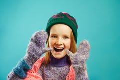 Портрет жизнерадостной девушки ребенка носит mittens зимы, теплый свитер, шляпу с pompom и openwork шарф накидки на сини стоковое изображение