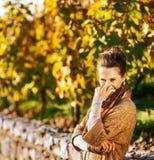 Портрет жизнерадостной женщины в парке осени пряча за шарфом Стоковая Фотография