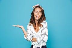 Портрет жизнерадостной женщины 20s нося вскользь одежду усмехаясь a стоковое изображение