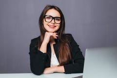 Портрет жизнерадостной коммерсантки сидя на таблице в офисе и смотря камеру Стоковая Фотография RF