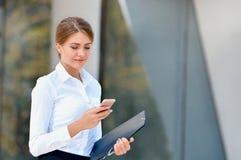 Портрет жизнерадостной молодой женщины говоря на smartphone outdoors Стоковое фото RF