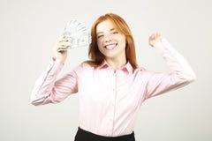 Портрет жизнерадостной молодой женщины держа пук 100 долларовых банкнот и празднуя в выигрывая представлении, руках вверх поднял  стоковая фотография