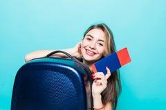 Портрет жизнерадостной молодой женщины одетой в одеждах лета держа паспорт с билетами летания пока стоящ с чемоданом стоковая фотография rf