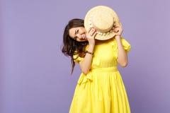 Портрет жизнерадостной усмехаясь молодой женщины в желтой стороне заволакивания платья со шляпой лета на пастельном фиолете стоковое изображение