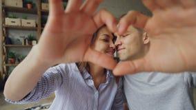 Портрет жизнерадостных многонациональных пар делая сердце с их руками, смотрящ камеру и усмехаться романтично видеоматериал